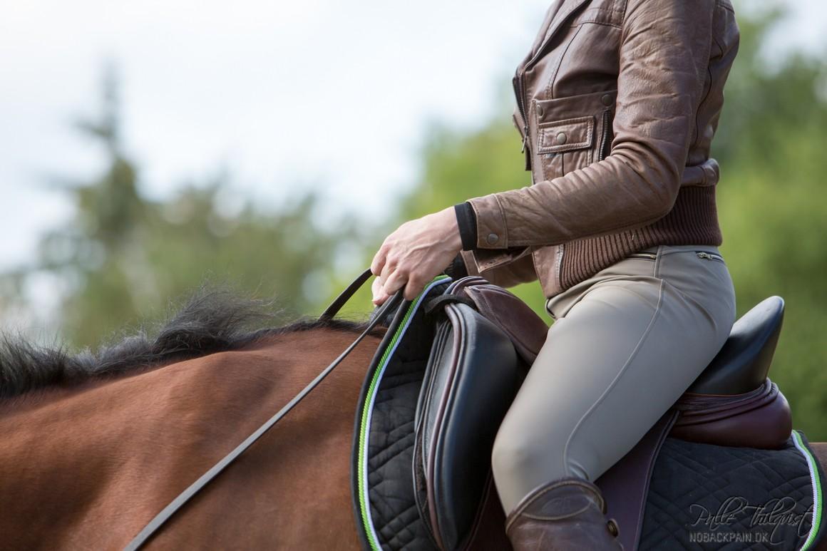 Sadlen ligger her en smule i bagvægt på Noller. Det gør at jeg skal sveje i ryggen for ikke at falde tilbage. Min vægt kommer til at være lidt for langt bagude i sadlen. Jeg skal kæmpe lidt for at holde benene i den rette position.